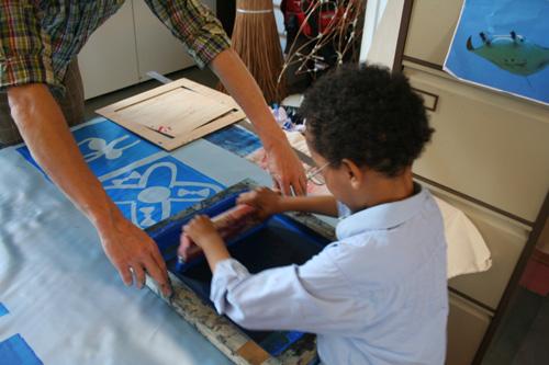 Children screen printing design onto textiles