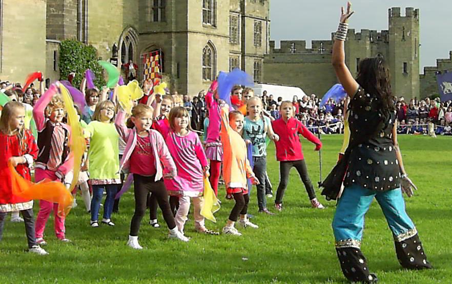 School children performing indian dancing with teacher