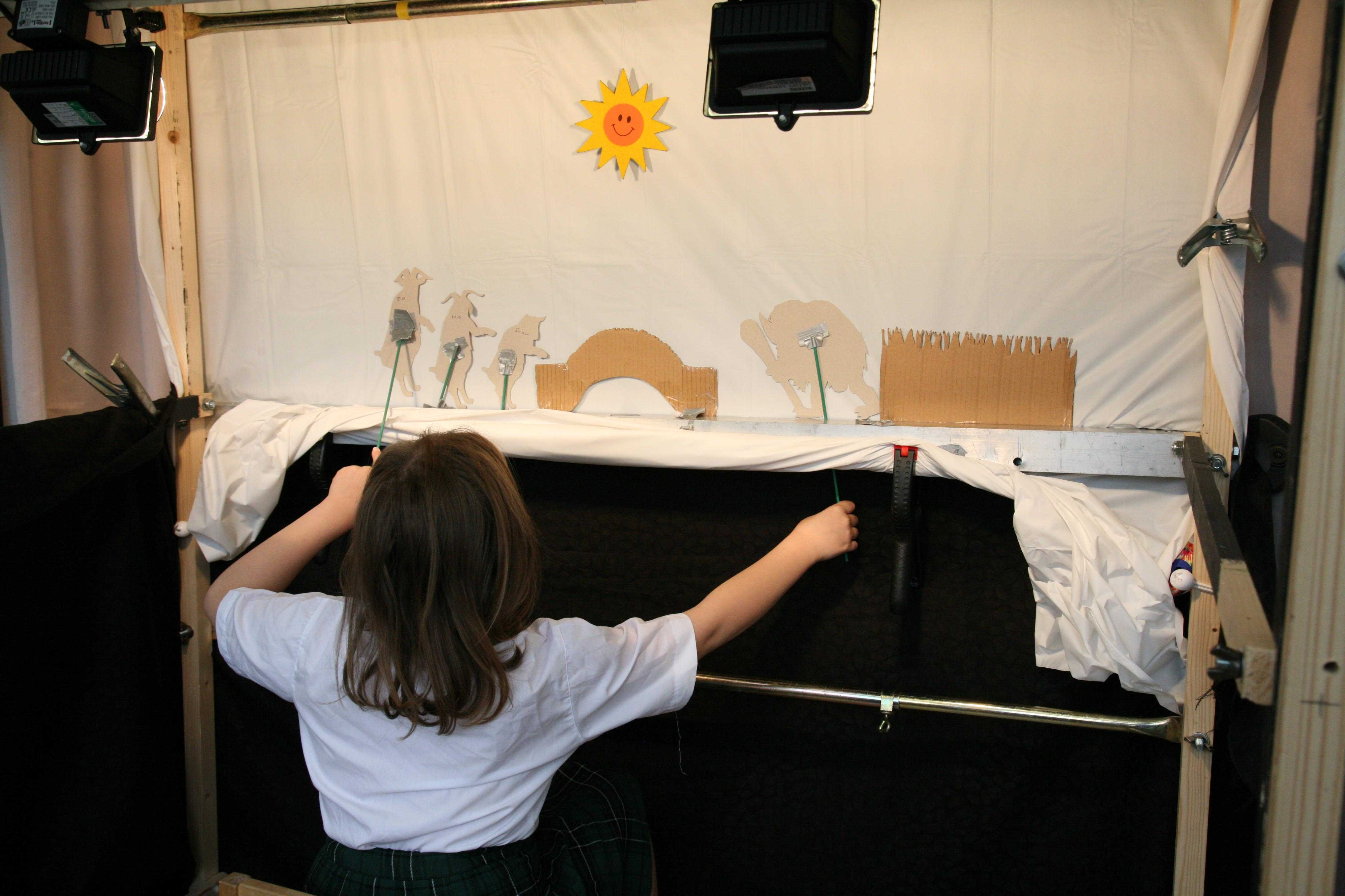 School children making shadow puppet characters out of cadrboard