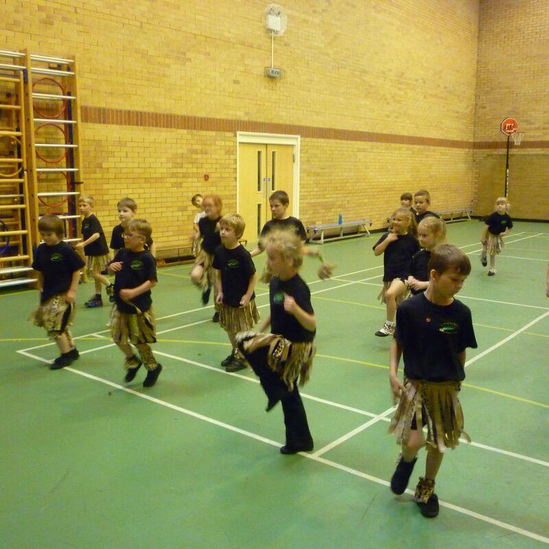 Children in hall doing african dancing