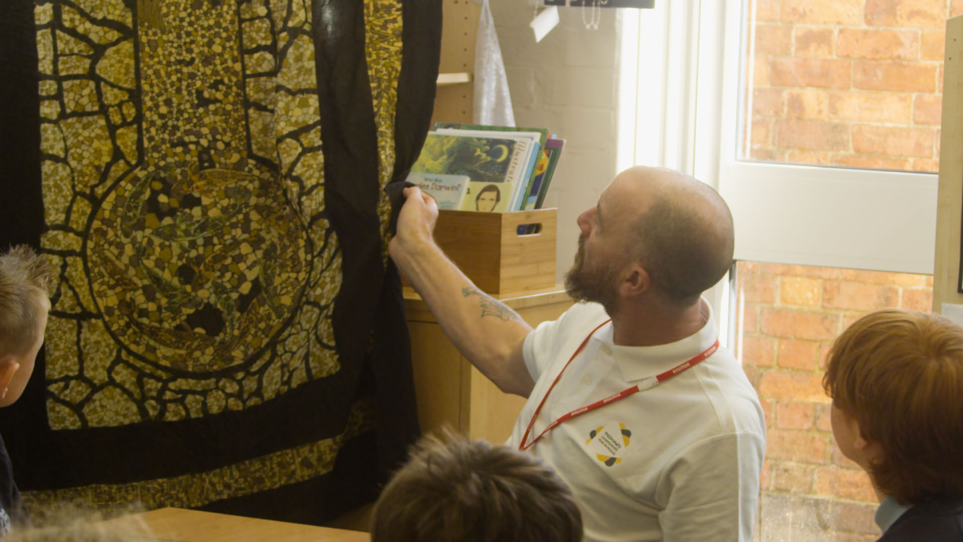 Teacher showing a black and white african textile work