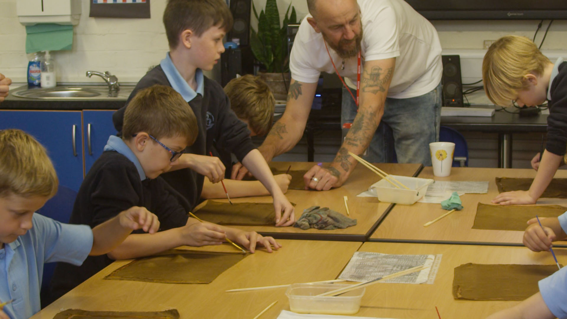 Teacher showing children how to draw out design for textile printing