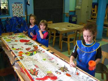 Children silk screen printing colourful designs onto textiles