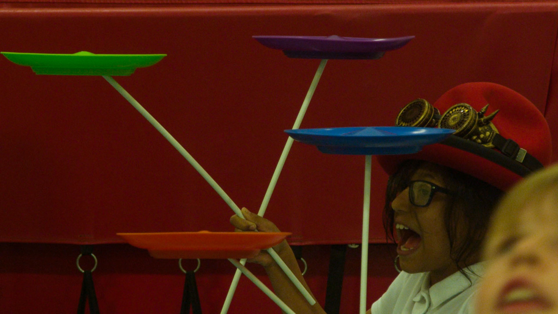 School children balancing different coloured plates in circus workshop