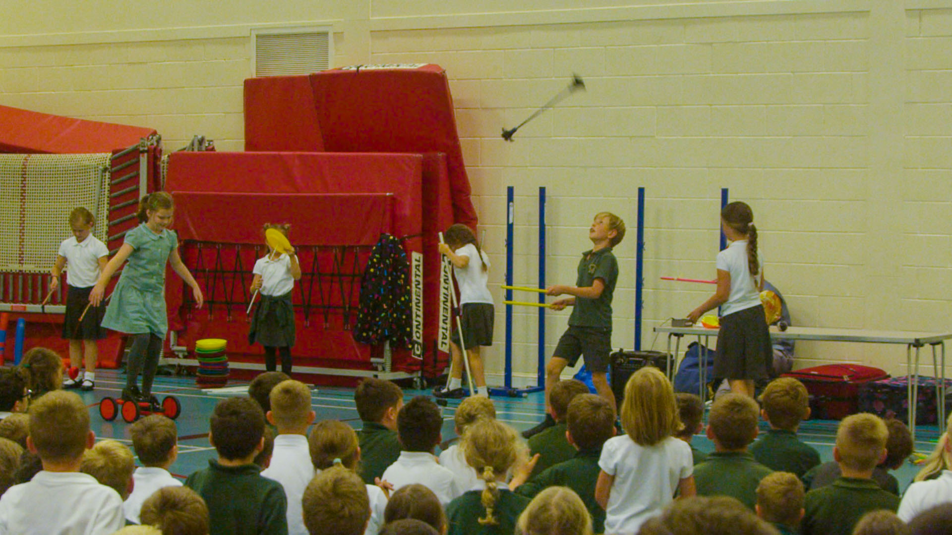 School children performing circus skills in school hall