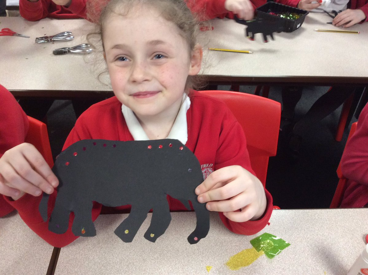 Children cutting out elephant shadow puppetry on cardboard