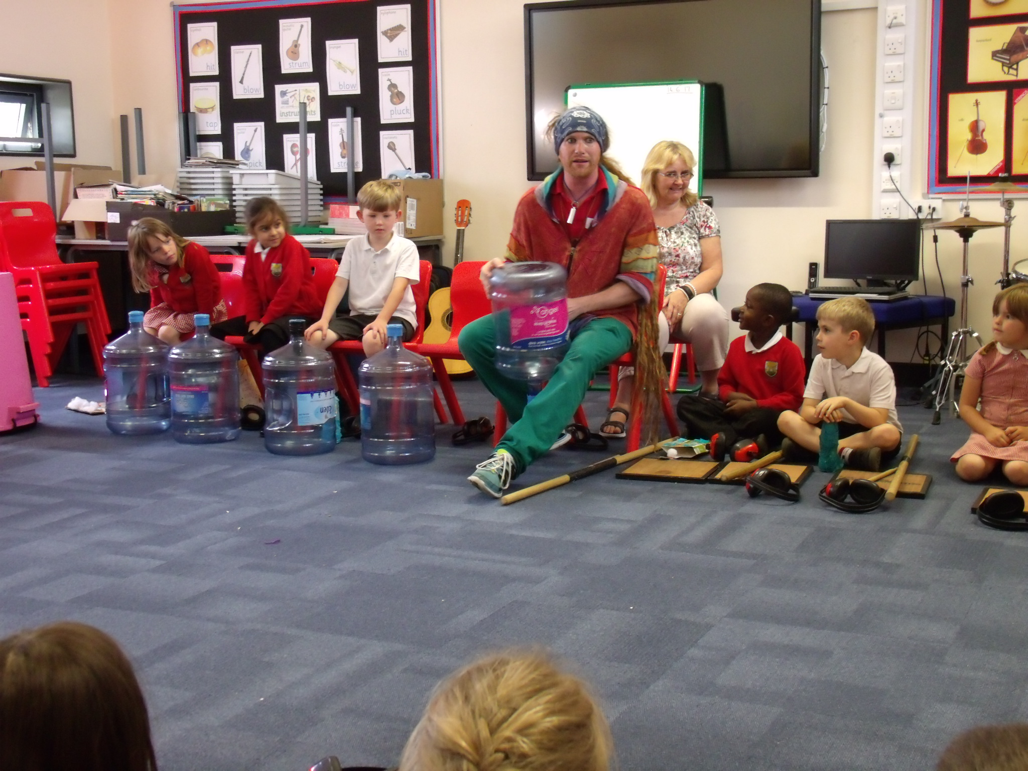 Teacher demonstrating how to play musical instruments made out of bottles