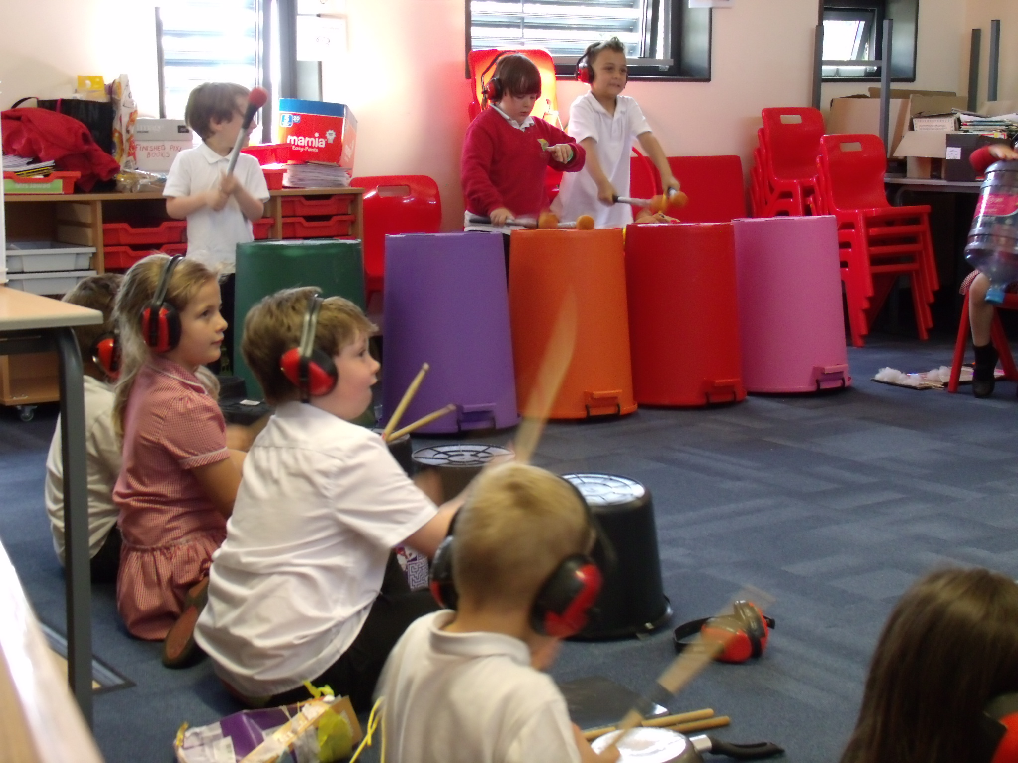 School children playing musical instruments made out of household objects
