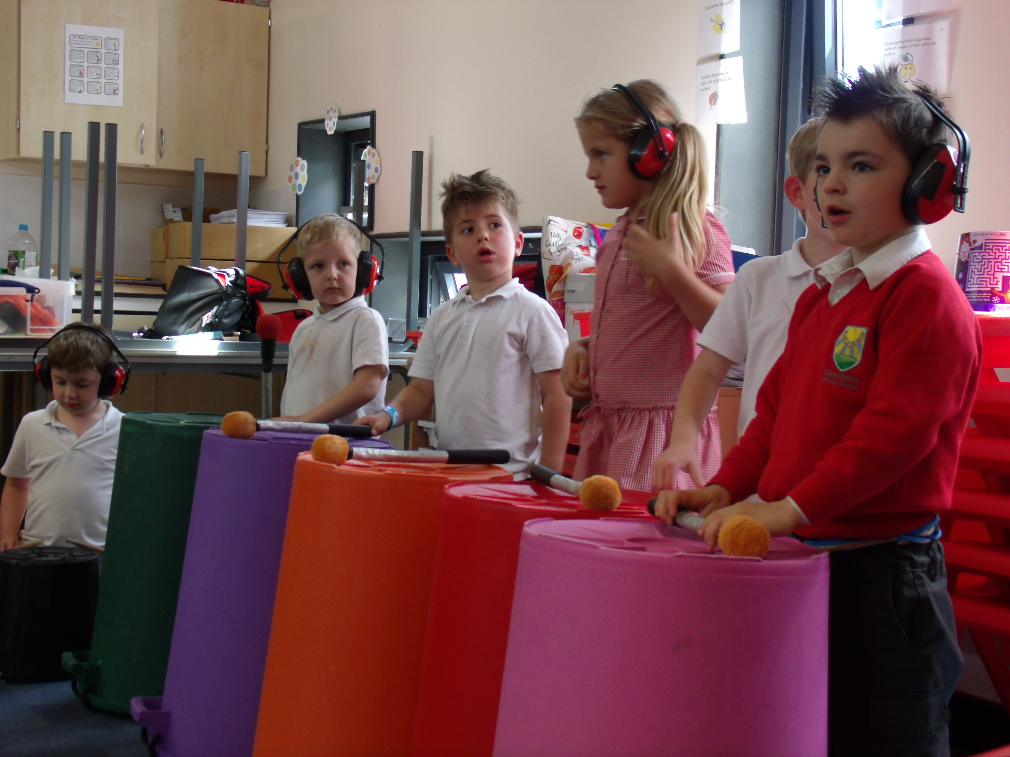 School children playing music on large colourful empty bins