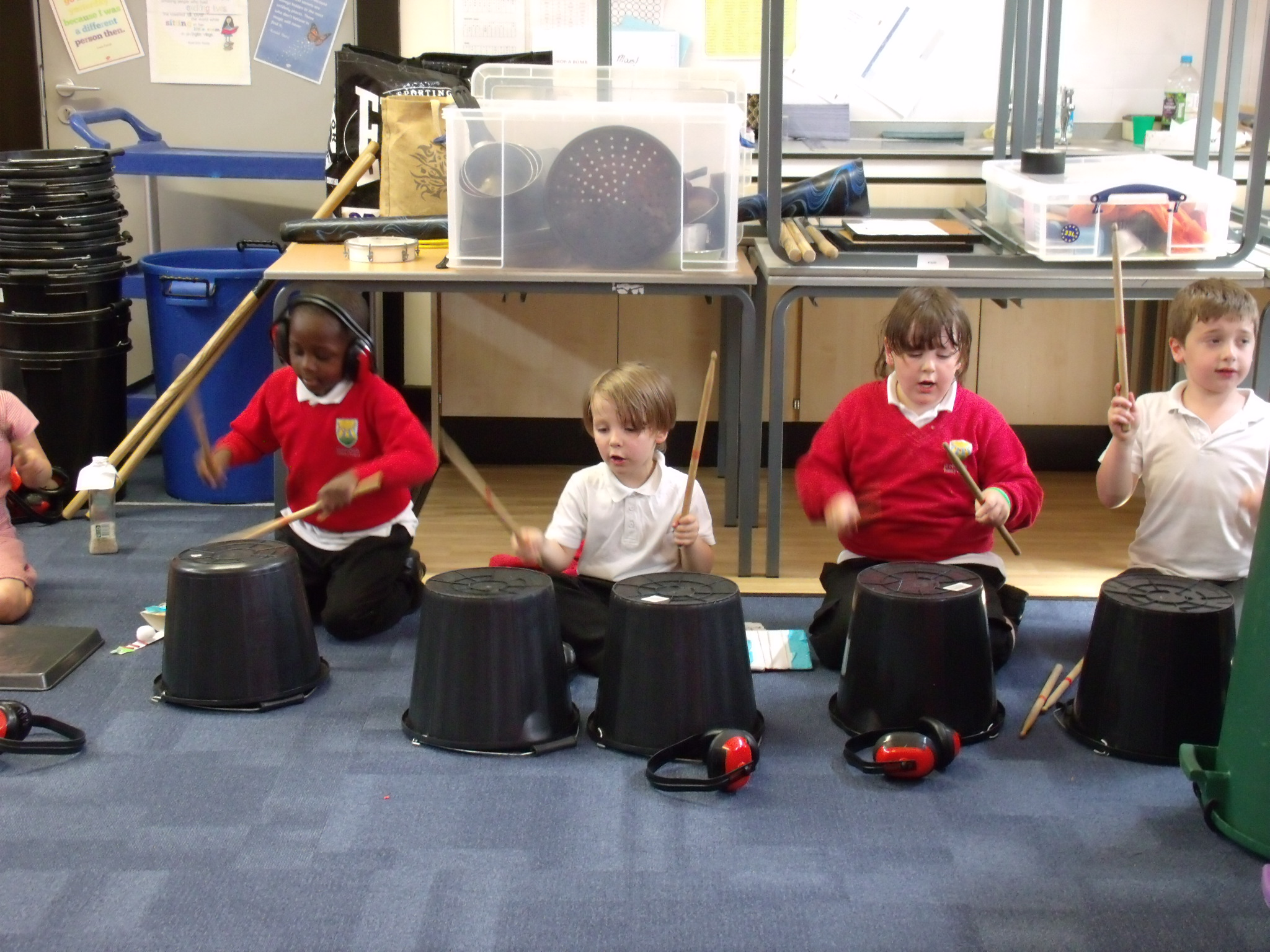 School children playing music on large empty buckets