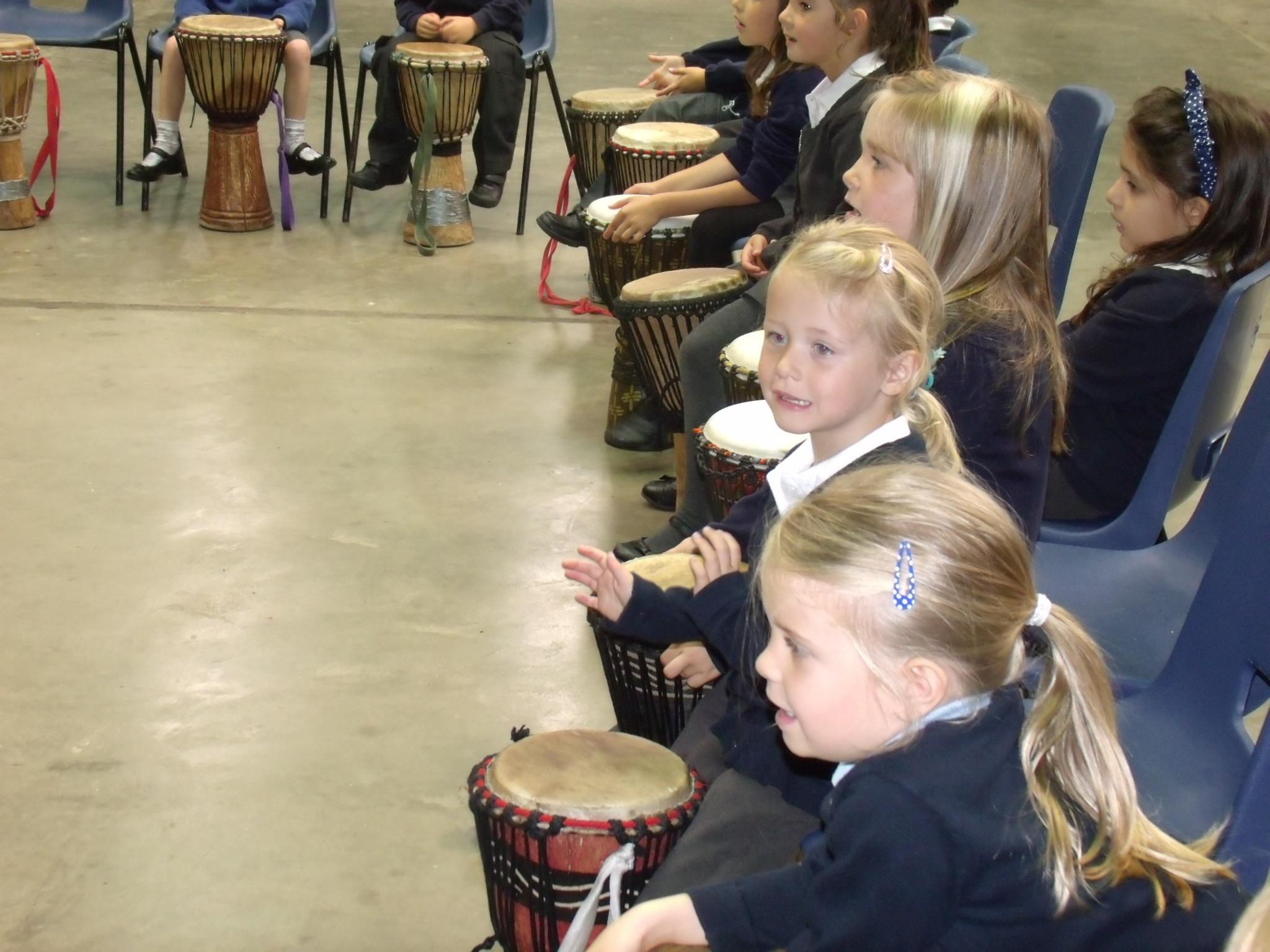Children in school playing African Drums