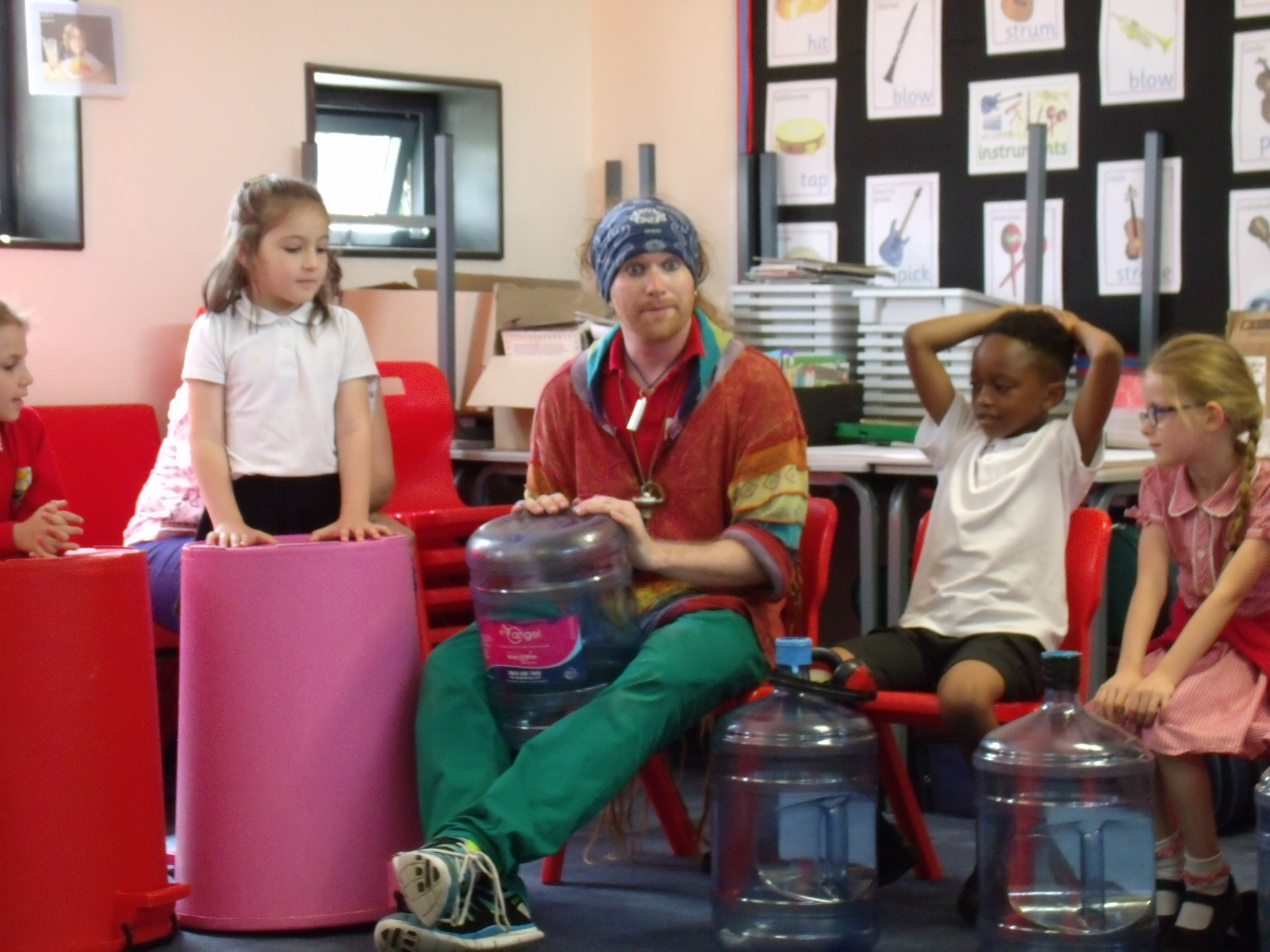 School children and teacher playing music on large colourful empty bins and bottles