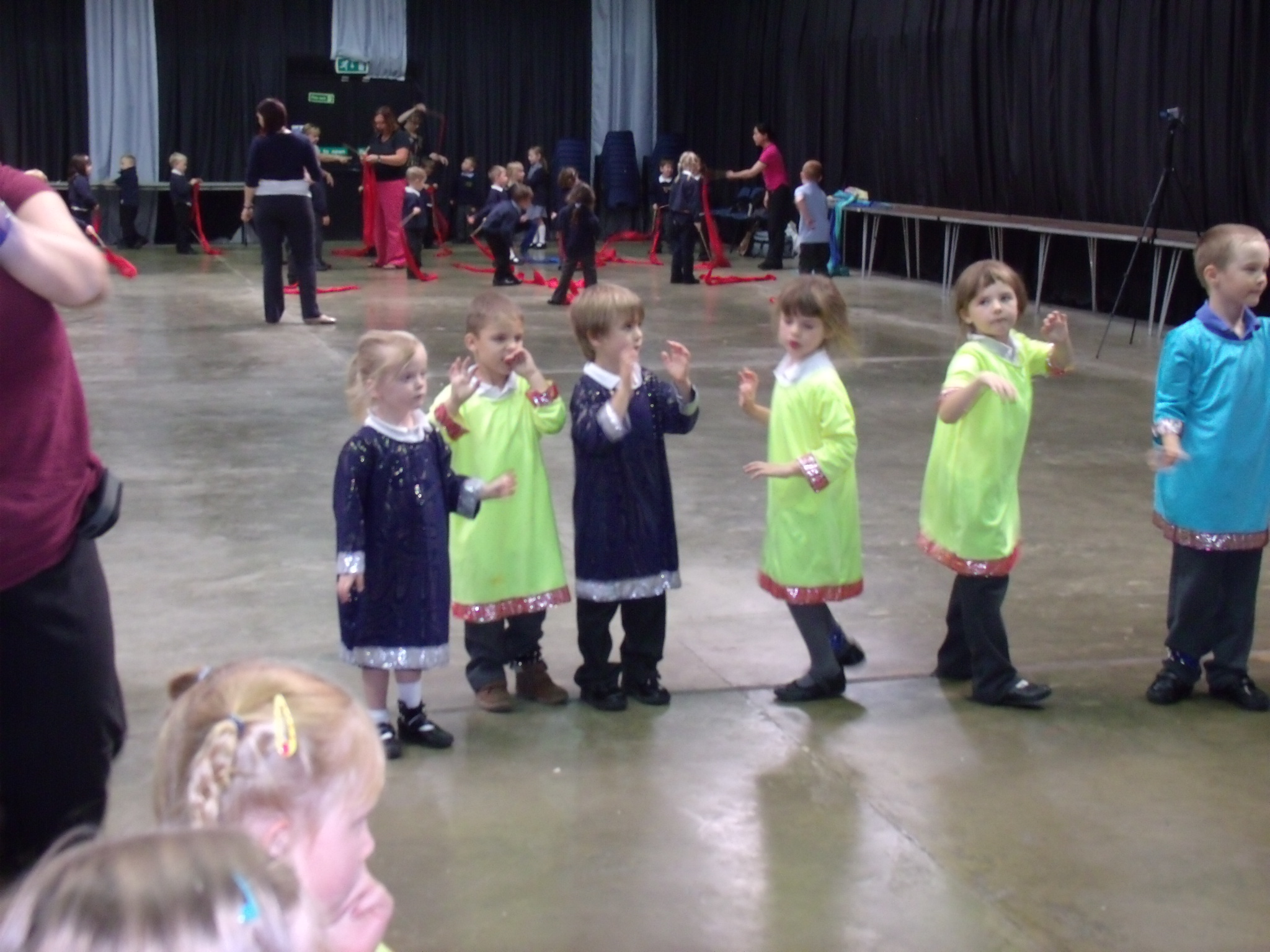 School children dressed in bright Indian clothing learning Indian dance