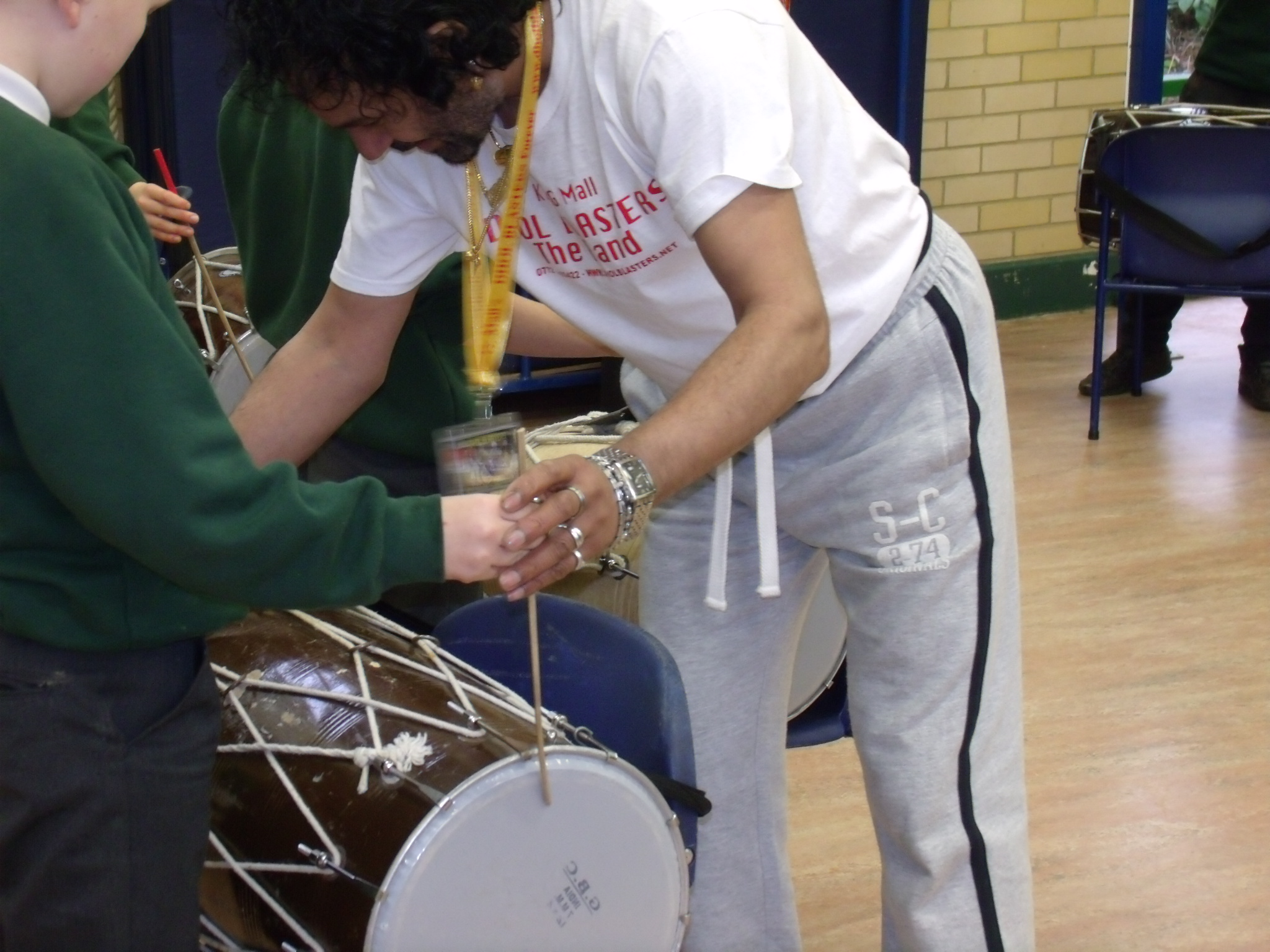 Class of children being taught how to use an Indian drum