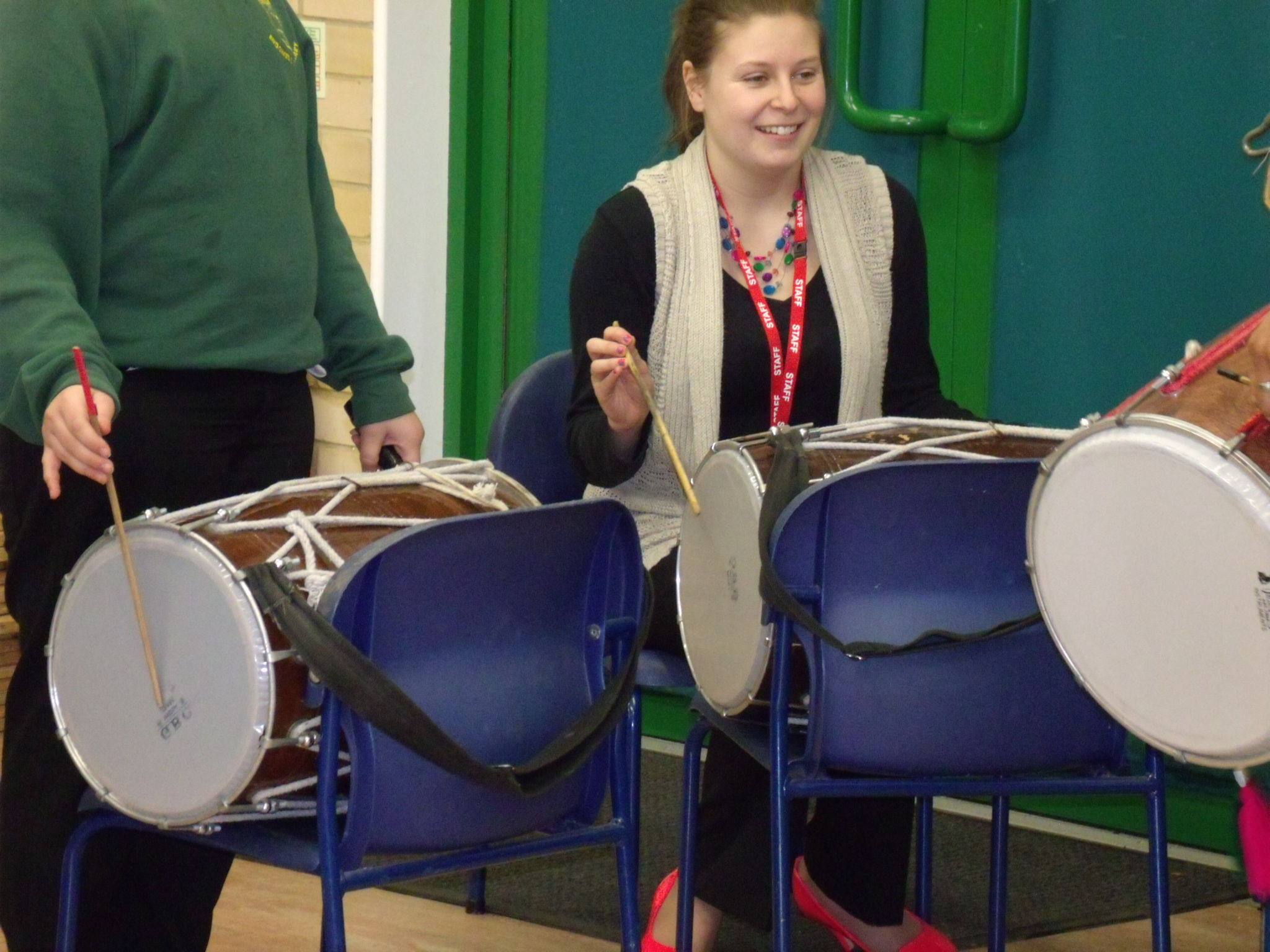 Teacher learning how to play indian drum in school hall on chair