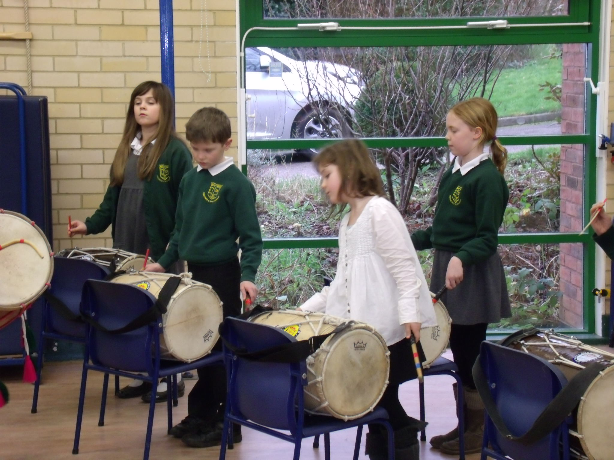 School children playing Indian drums in school hall on chairs