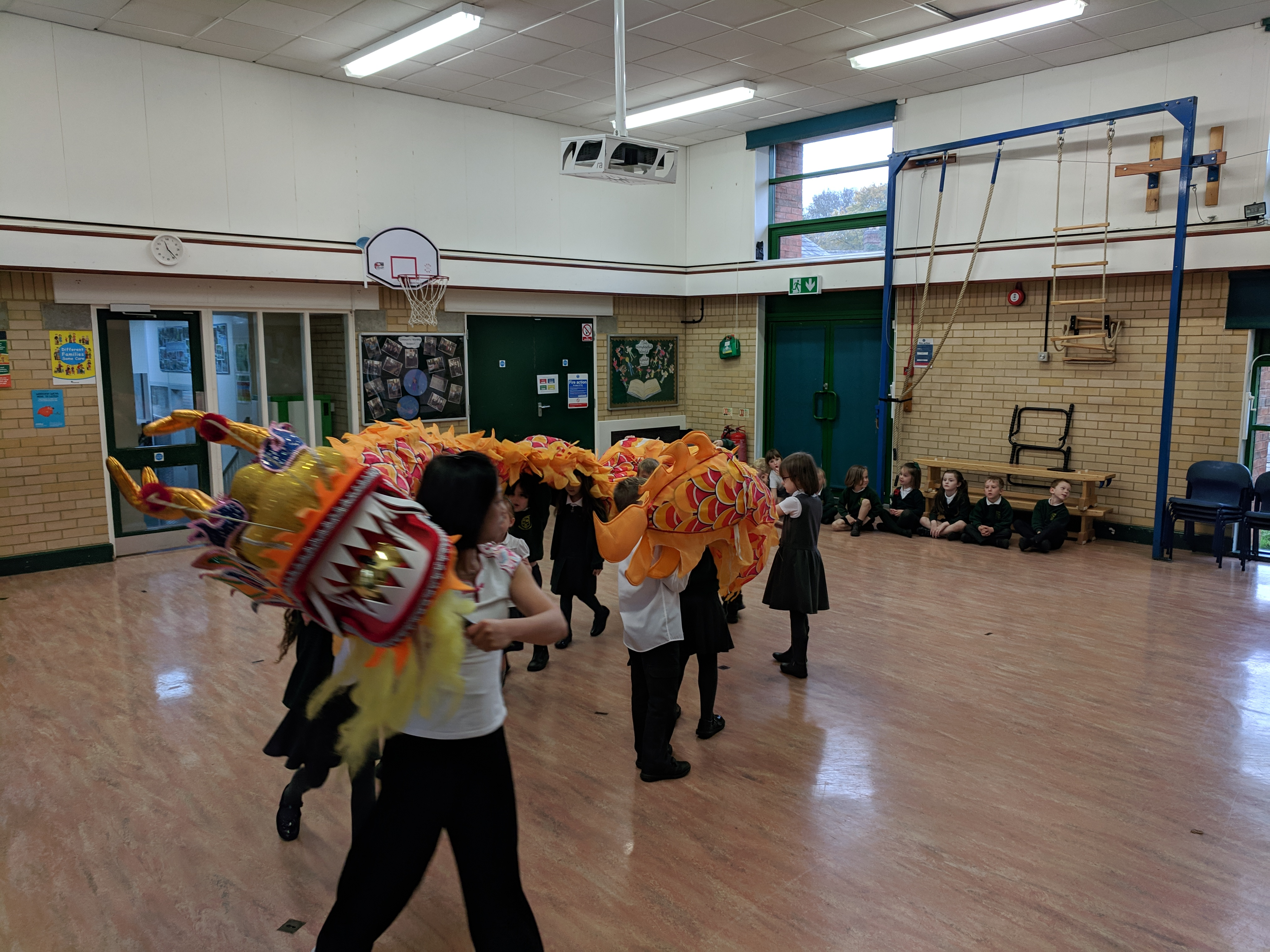 School children dancing in hall with chinese dragon