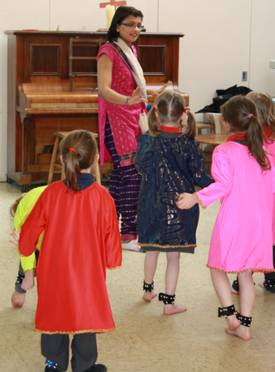 Children being taught by teacher Indian dancing wearing Indian dresses