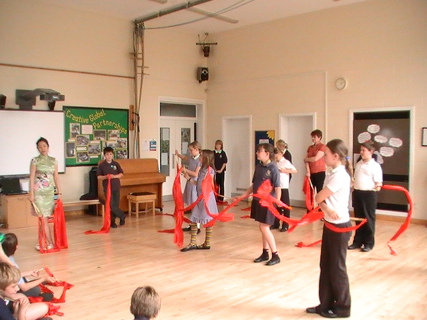 School children learning how to dance with Chinese dance ribbons