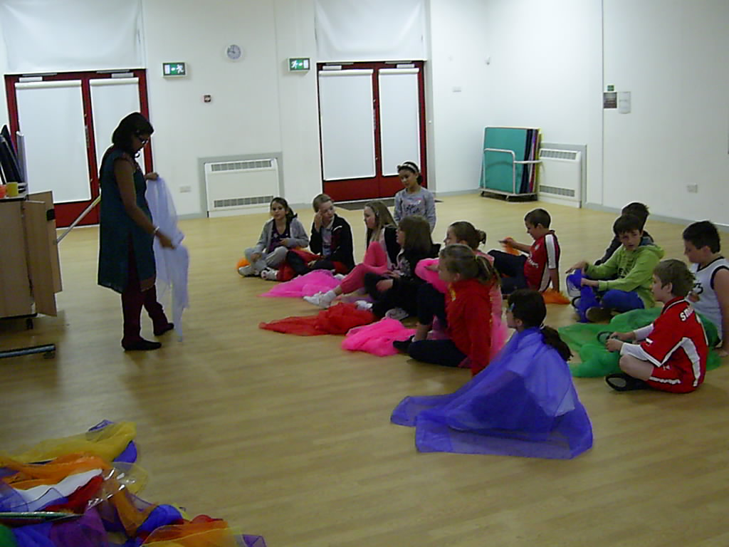School children sitting in school hall learning about indian textiles