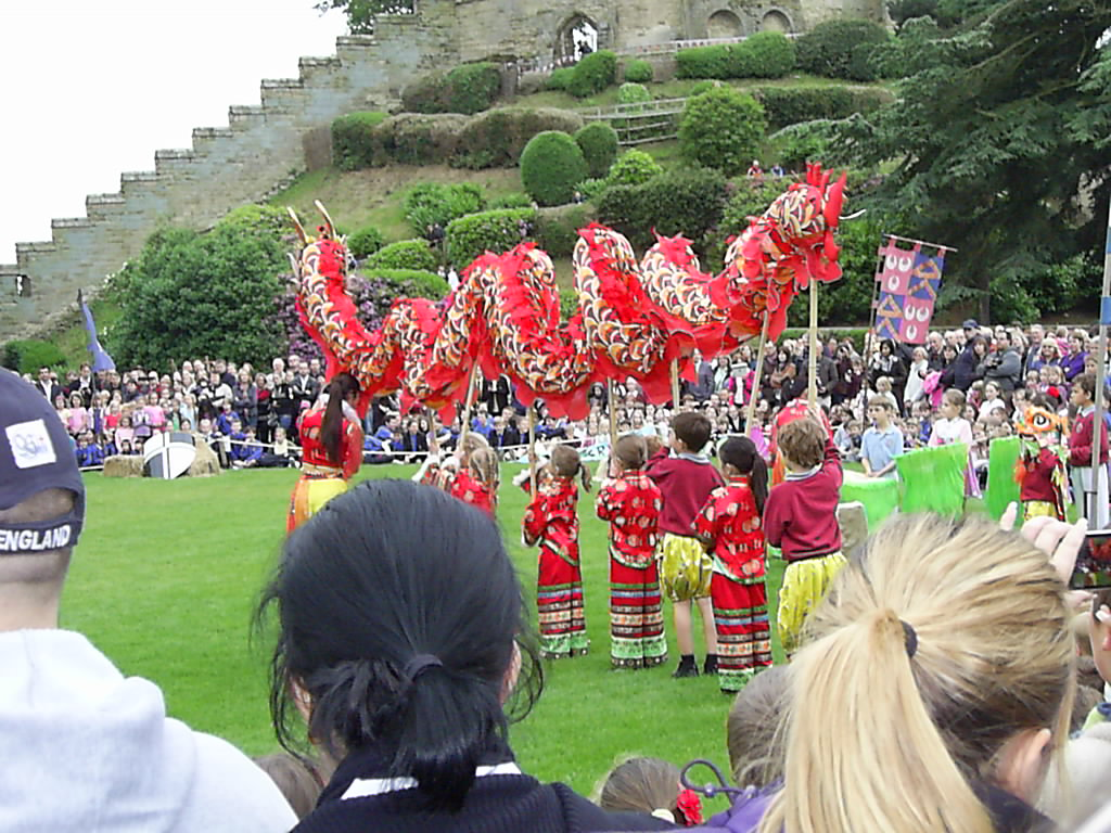 Schoool children chinese dragon dancing on school playing field