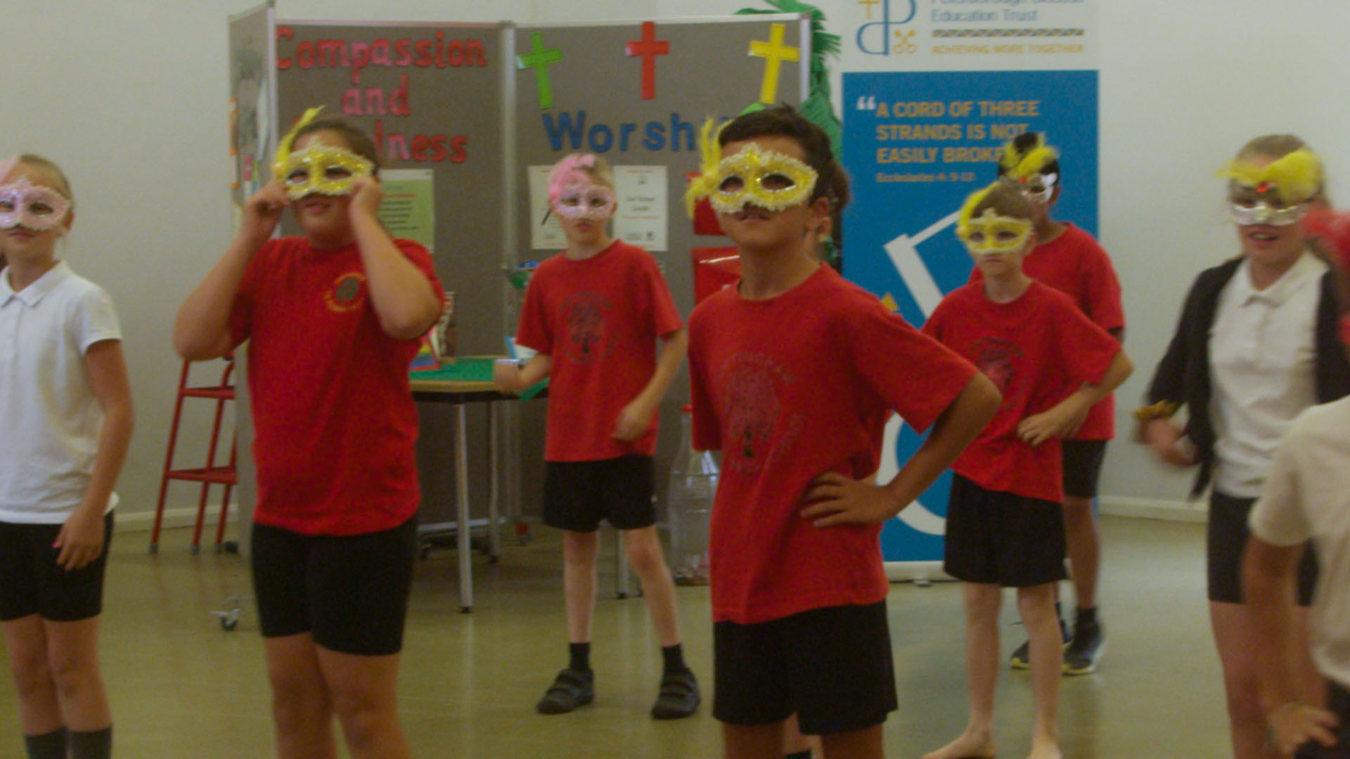 School children wearing dance masks for South American dance workshop