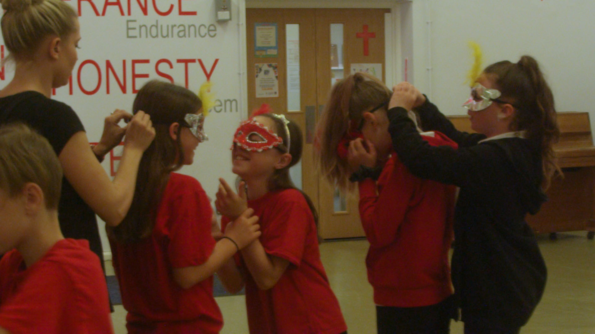 School children putting on masks for South American dance