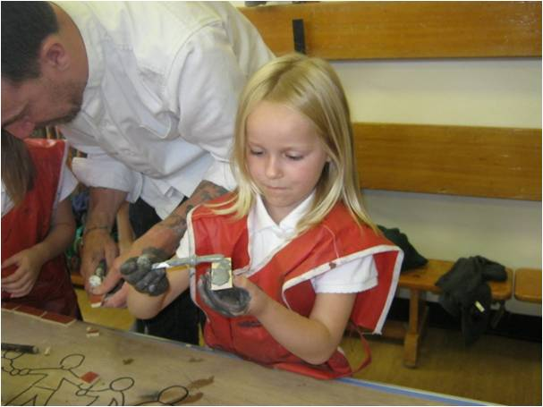 School children making mosaic pieces