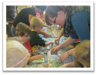 School children creating a mosaic with teacher