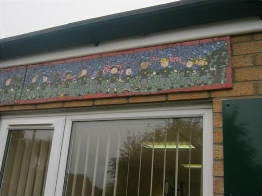Finished mosaic on wall featuring school children in a line