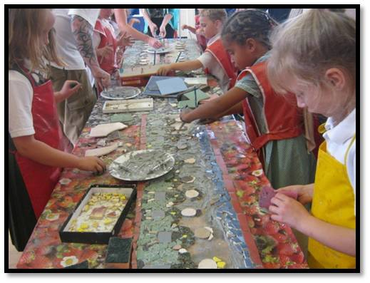 School children creating a mosaic on table with lots of different colours