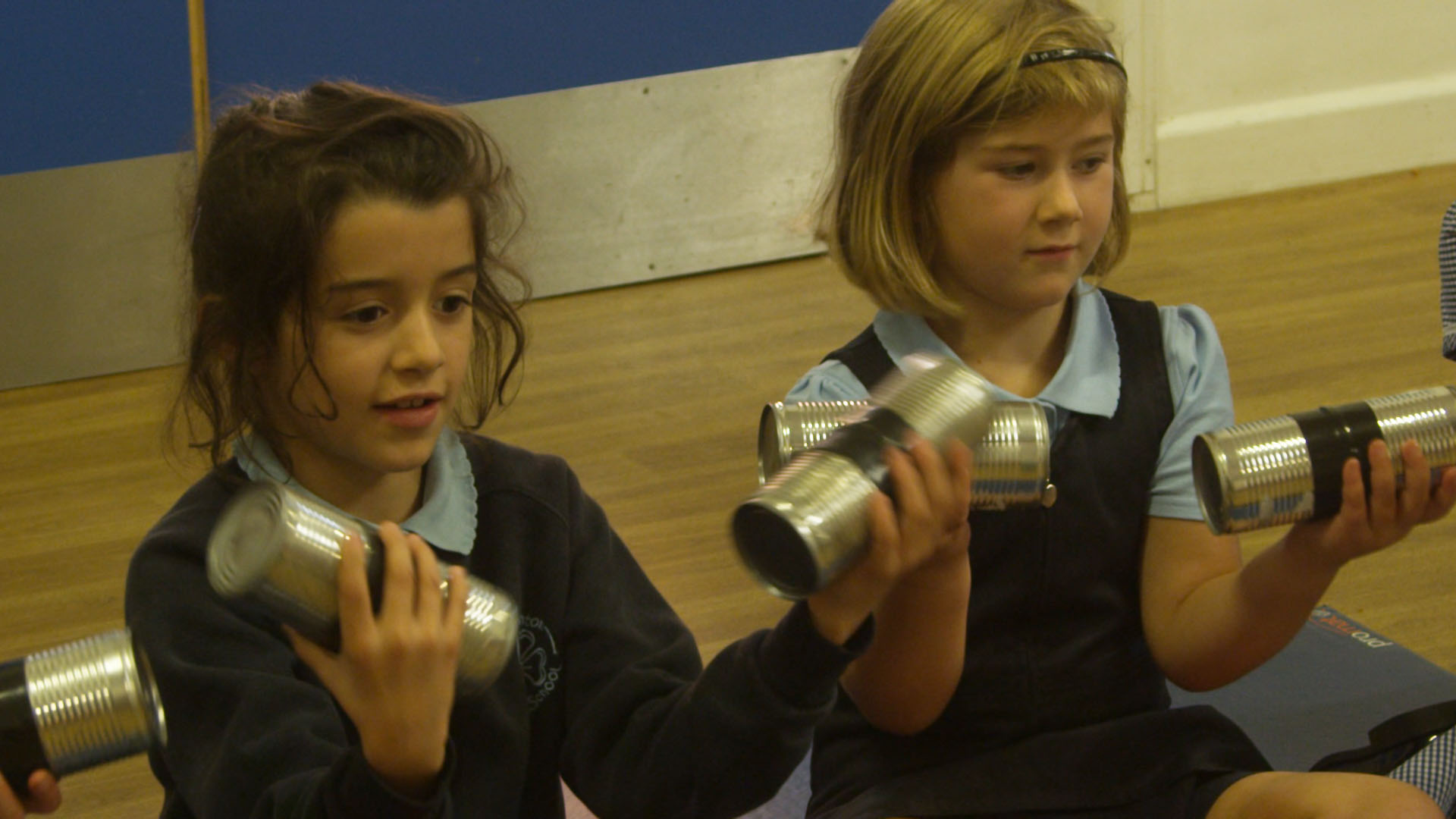 School children playing music on recycled tin cans