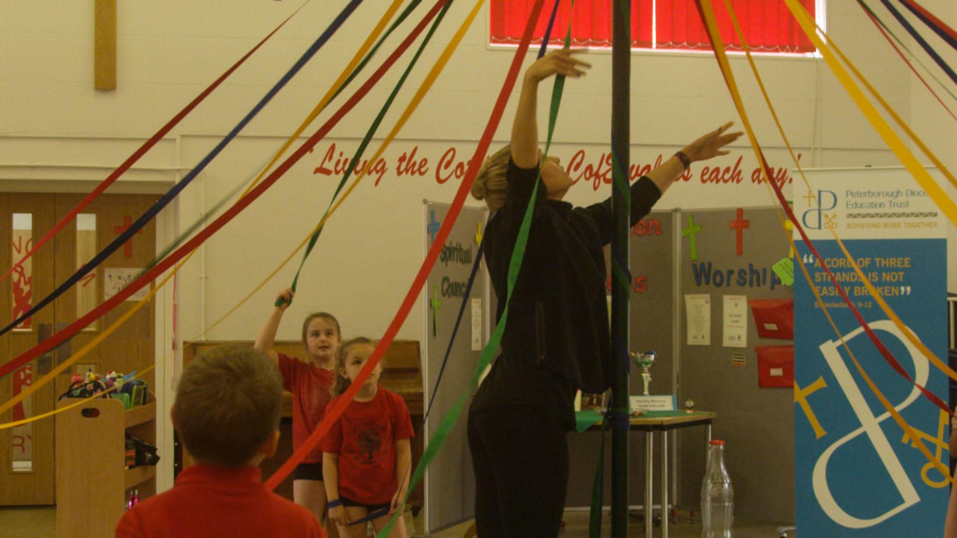 Teacher adjusting the strings on maypole
