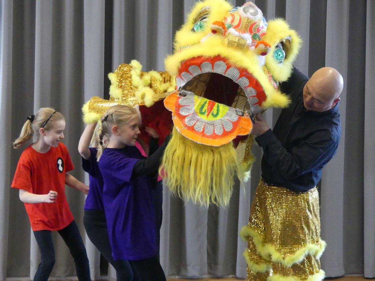 School children and teacher putting on yellow Chinese lion dance costume
