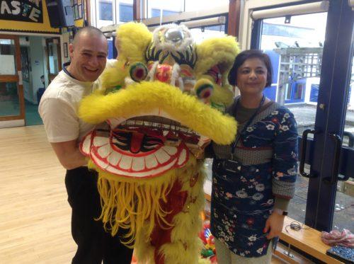 Teachers holding yellow lion dance costume