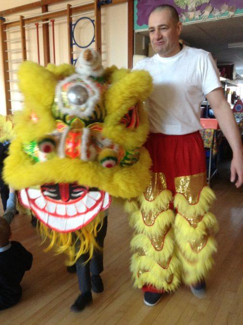 Teacher holding on yellow Chinese lion dance costume