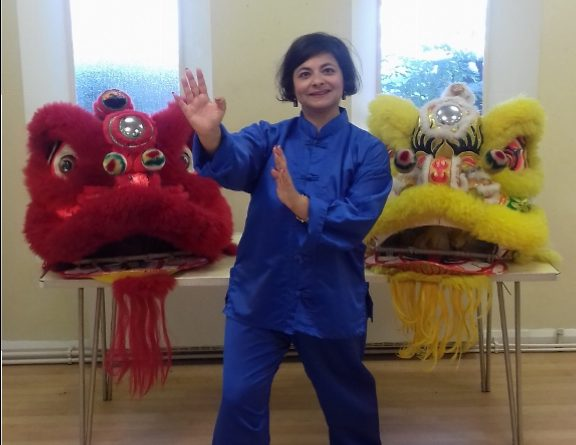 Yellow and red lion dance costumes on table with teacher
